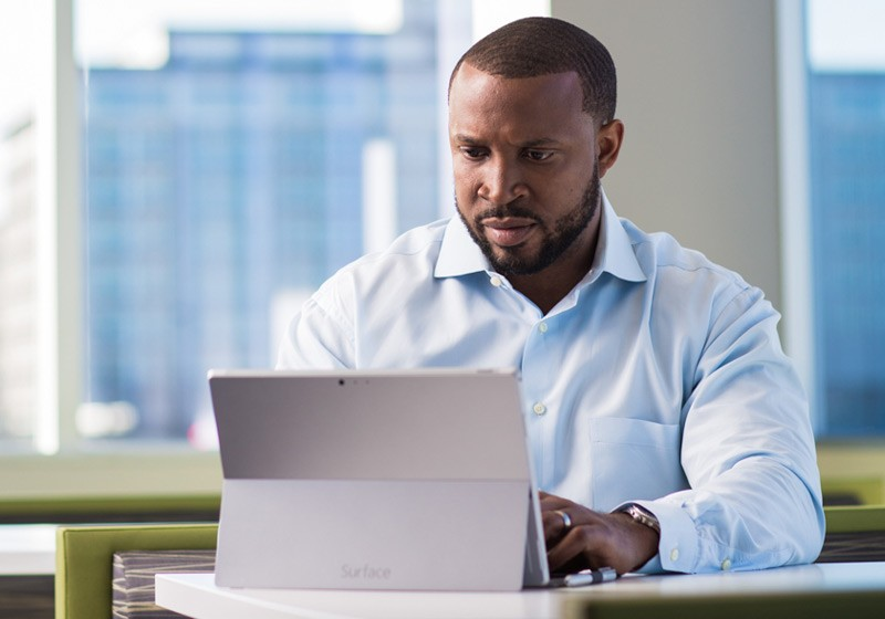 Business manager reviewing applications off of his Surface Pro mobile tablet device